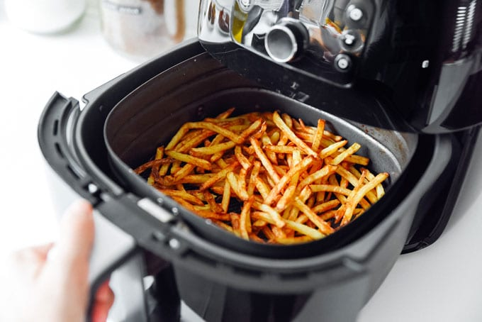 Making homemade French fries in an air fryer with a white background
