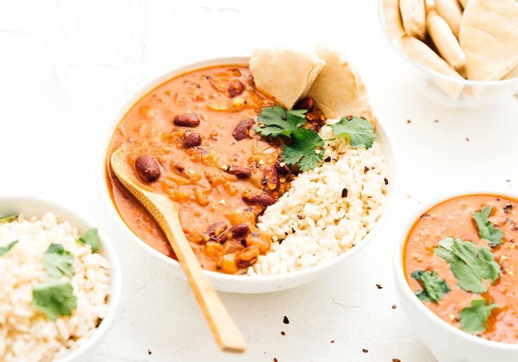 A bowl of coconut kidney bean curry, rice, and bread surrounded by bowls filled with various ingredients