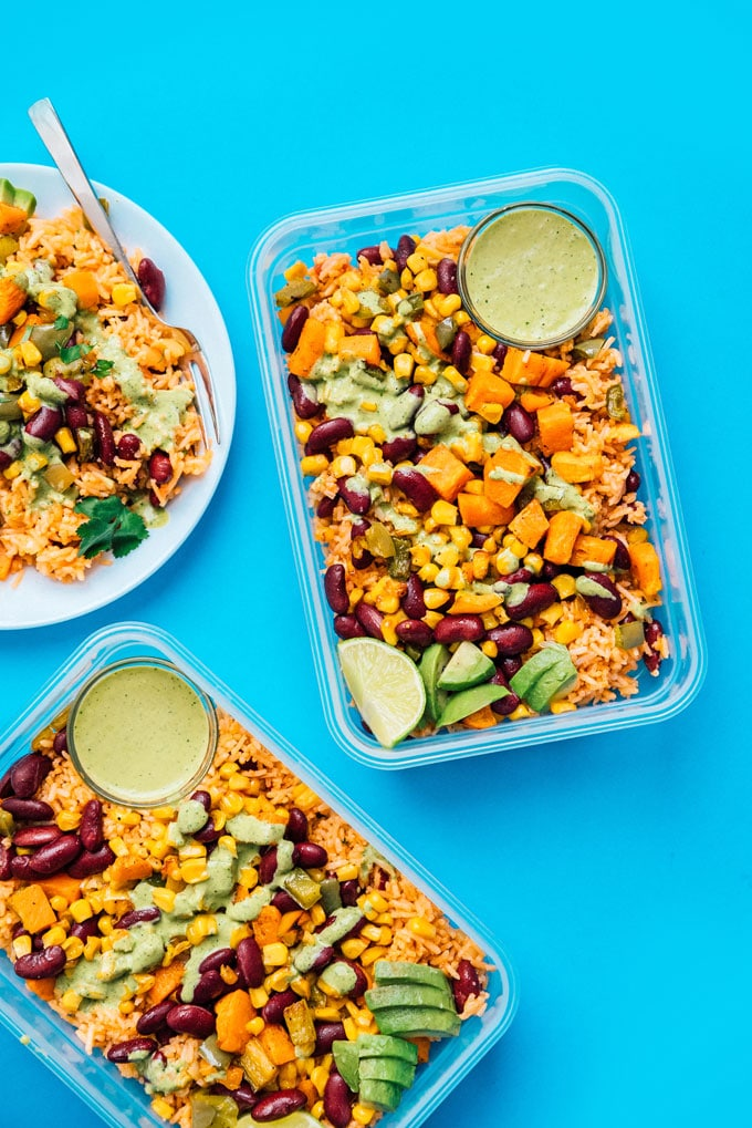 Rice and beans meal prep on a blue background - Serving up some easy vegetarian meal prep today in the form of roasted veggies with Spanish rice, tossed in a creamy cilantro dressing!