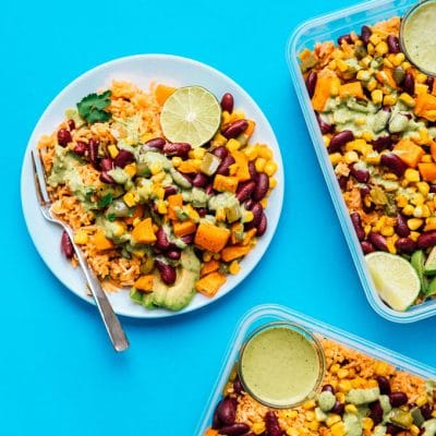 Meal prep on a blue background - Serving up some easy vegetarian meal prep today in the form of roasted veggies with Spanish rice, tossed in a creamy cilantro dressing!