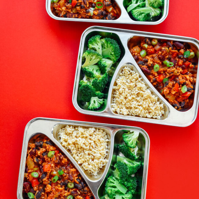 Meal prep containers with broccoli, chili, and bulgur on a red background - This vegan Tempeh Chili Meal Prep is ready in 30 minutes and takes care of lunch for the week (plus it's like...really tasty).