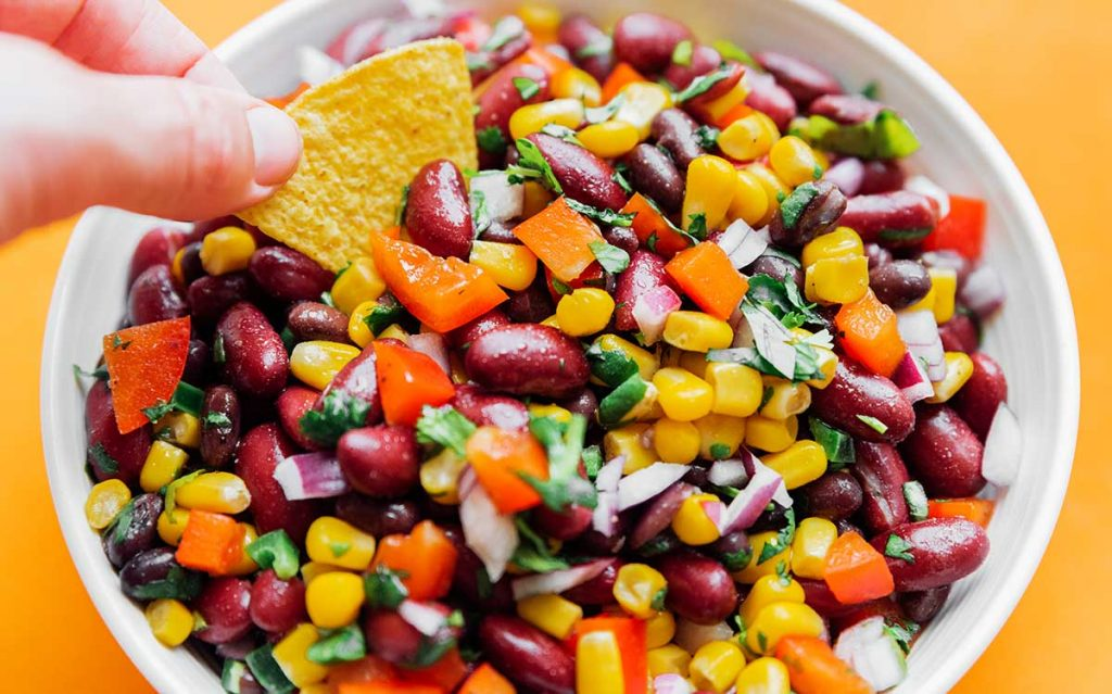 Bean salad in a bowl on an orange background