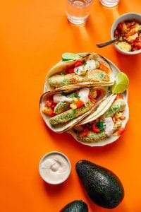 Vegetarian avocado tacos on an orange background - Creamy, crispy avocado tacos with fresh pineapple salsa and a quick yogurt sauce, perfect for your vegetarian Taco Tuesdays!