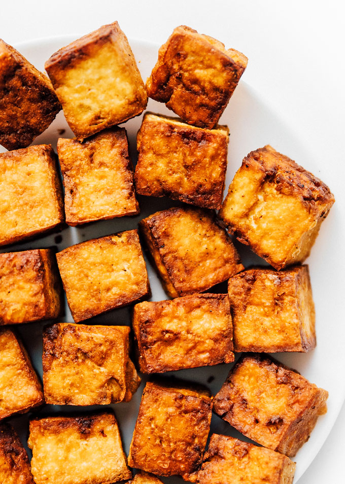 Crispy tofu cubes on white background