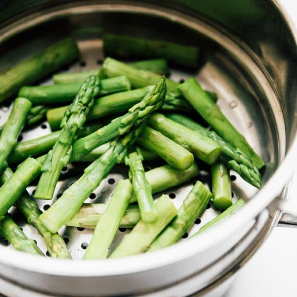 Asparagus in a steaming basket - The ultimate guide on how to cook asparagus! How to cook asparagus in the oven, in the microwave, or by blanching, steaming, or sautéing.