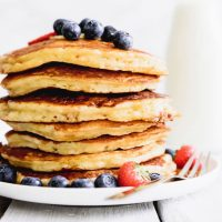 Stack of the best buttermilk pancakes with berries on a white background.
