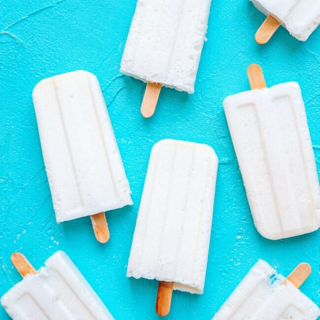 Marshmallow Coconut Popsicles recipe with white homemade popsicles on a blue background.