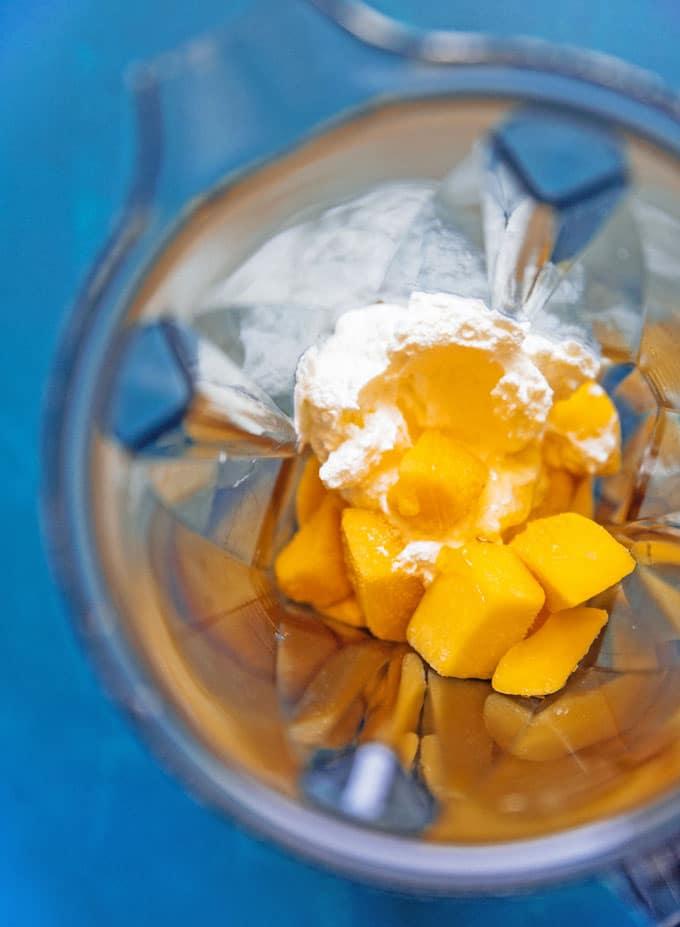 Ingredients to make mango lassi in a blender