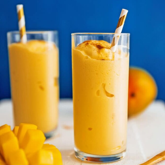 Mango lassi recipe in a glass with a straw