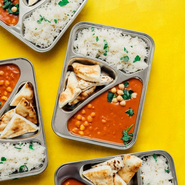 Vegan tikka masala with naan and rice in meal prep containers