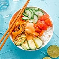 Vegan tomato tuna sushi bowl with rice, avocado, and cucumber in a bowl on a blue background