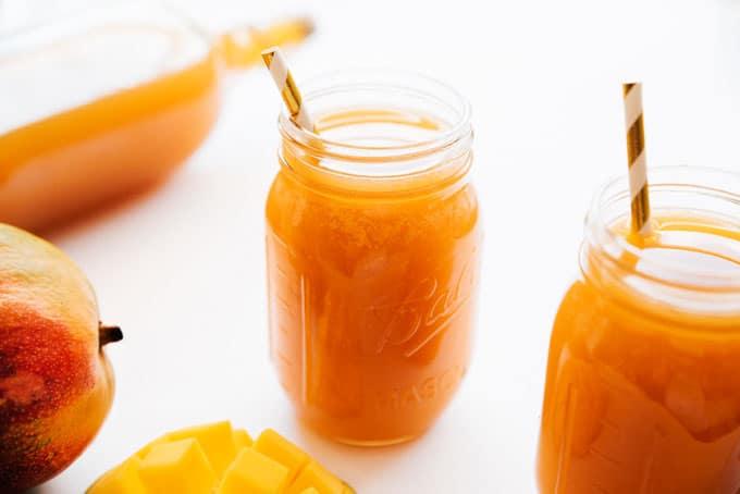 Homemade mango kombucha in a mason jar with a straw