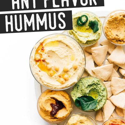 Different flavors of homemade hummus in bowls on a white background