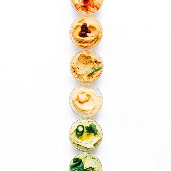 Rainbow variety of hummus in bowls on a white background