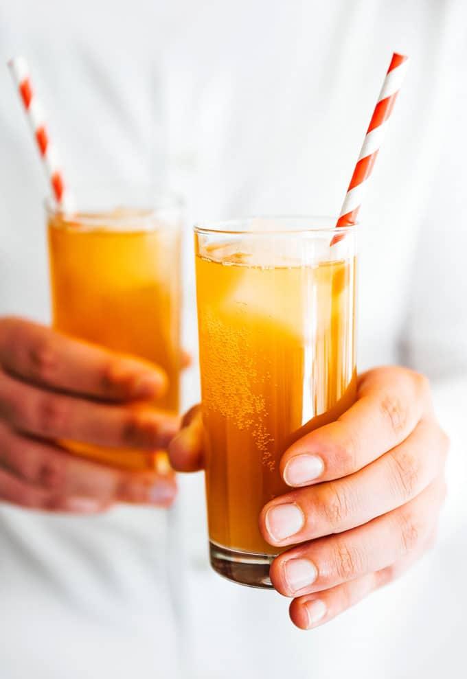 Hand holding ginger kombucha glasses