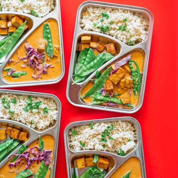 Thai red curry in a meal prep container with red background