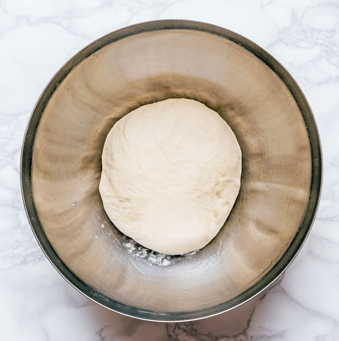 Kneaded pizza dough before rise on a marble background