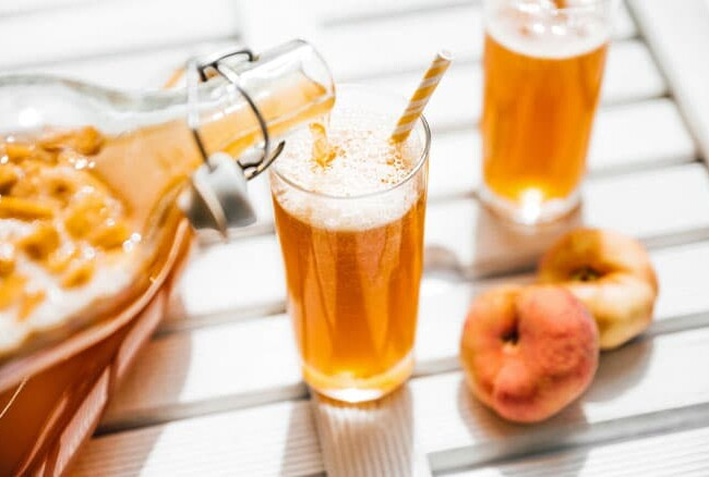 Poring fizzy kombucha into a glass with paper straw