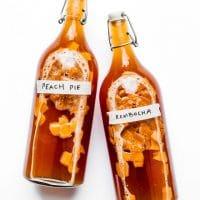 Peach kombucha in bottles on a white background