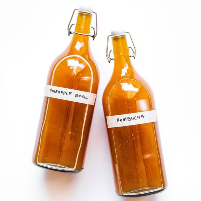 Pineapple kombucha in bottles on a white background