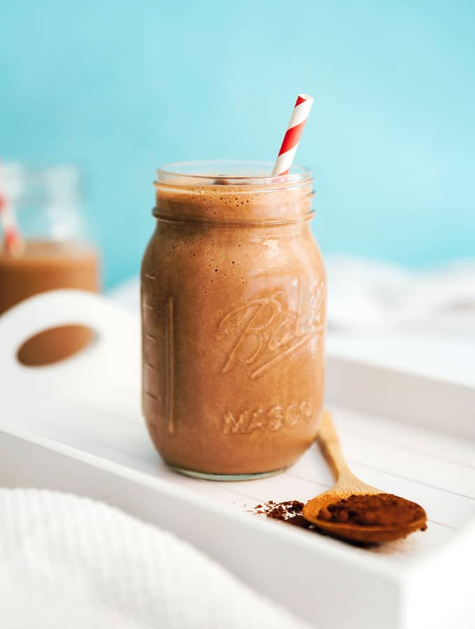 Tofu mocha smoothie in a glass with blue background