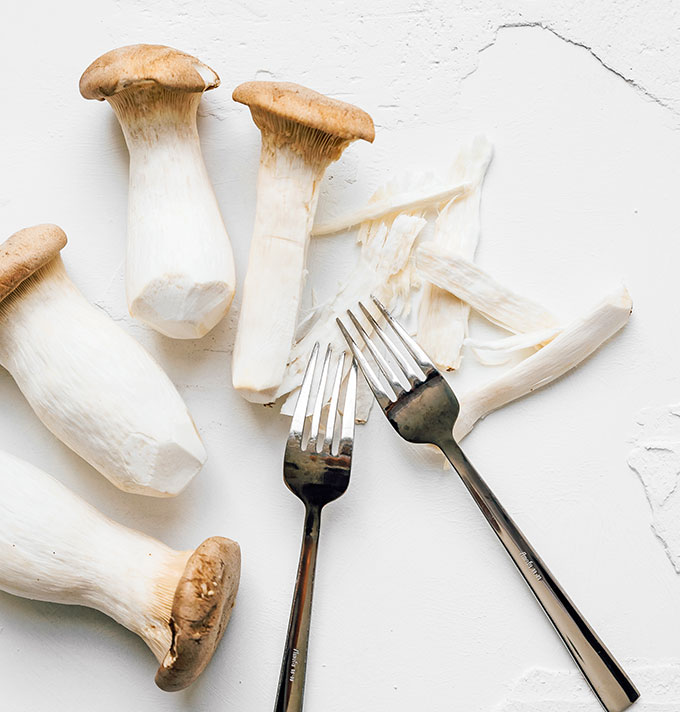 Shredding king oyster mushrooms with forks