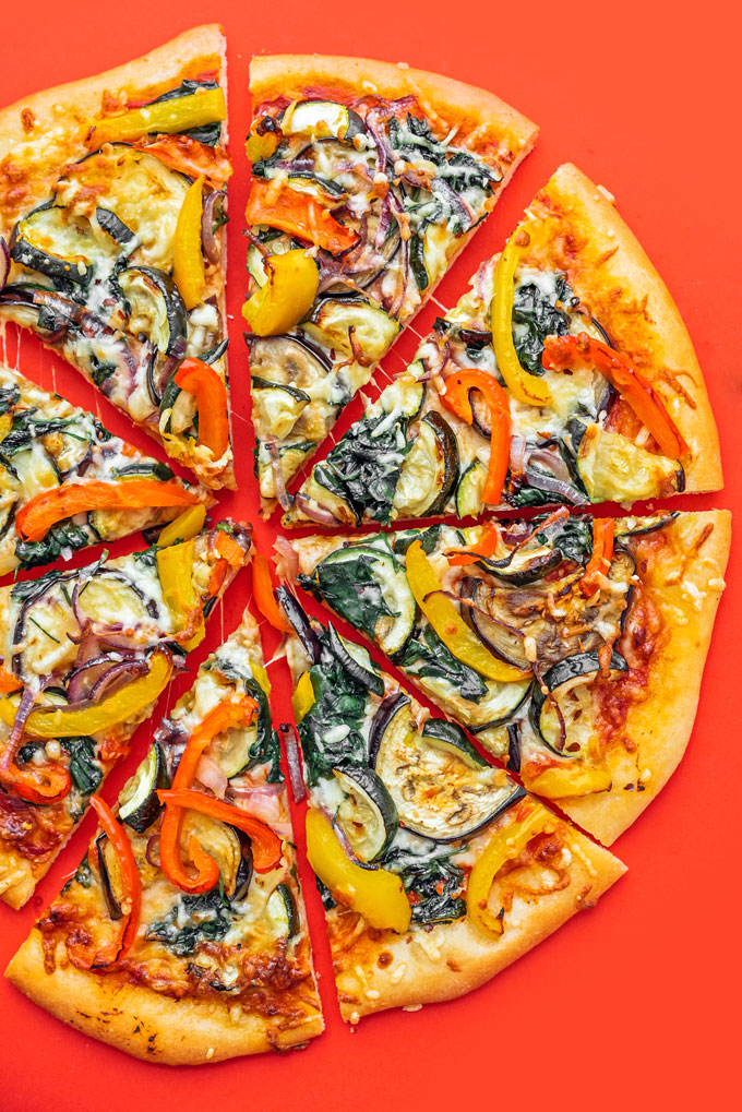 Veggie pizza slices on red background