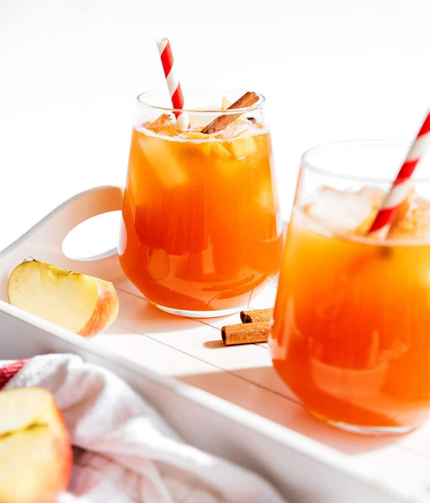 Apple cinnamon kombucha into a glass with a white background