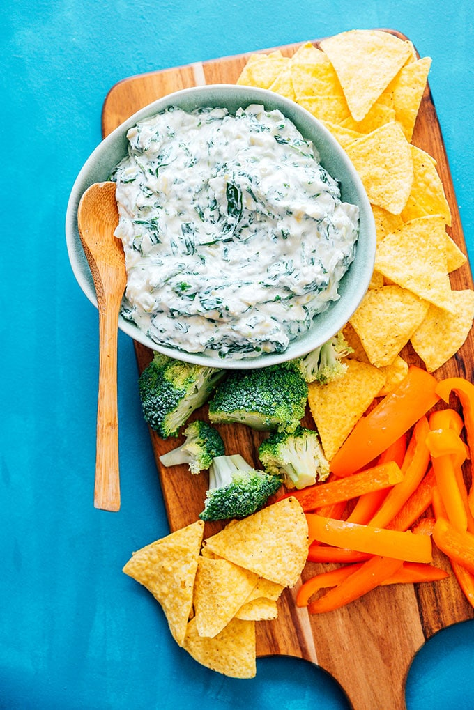 Healthy spinach artichoke dip in a bowl with broccoli, chips, and bell pepper
