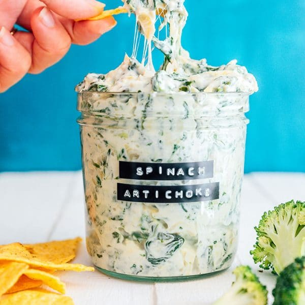 Spinach artichoke dip in a jar with a cheesy dip