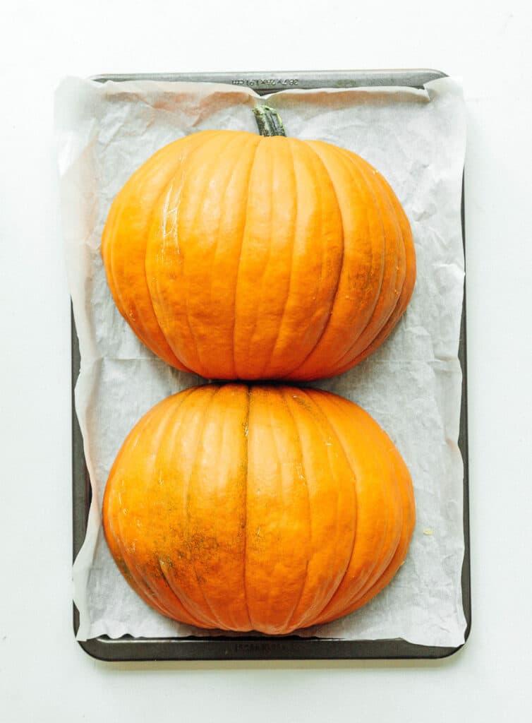 Two pumpkin halves on a baking sheet