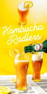 Kombucha radler in a glass with a lemon on a yellow background