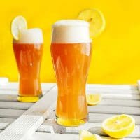 Kombucha shandy in a glass with a lemon on a yellow background