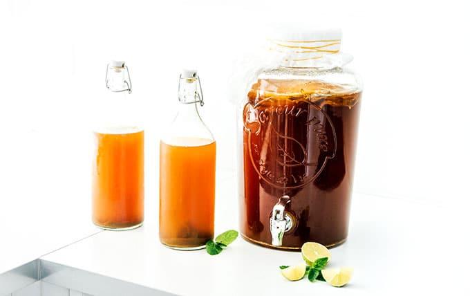 Mint lime kombucha in fermentation bottles with a jar of first fermentation kombucha
