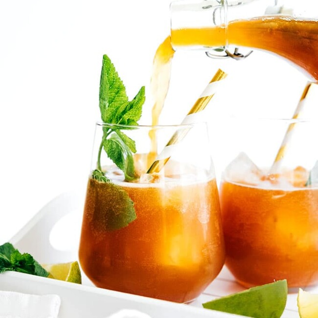 Pouring mojito flavored kombucha into a glass with ice and a paper straw