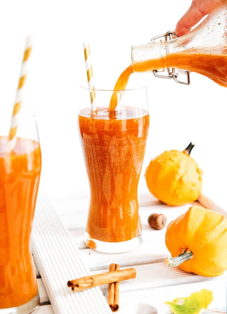 Pouring pumpkin spice kombucha in a glass on white background