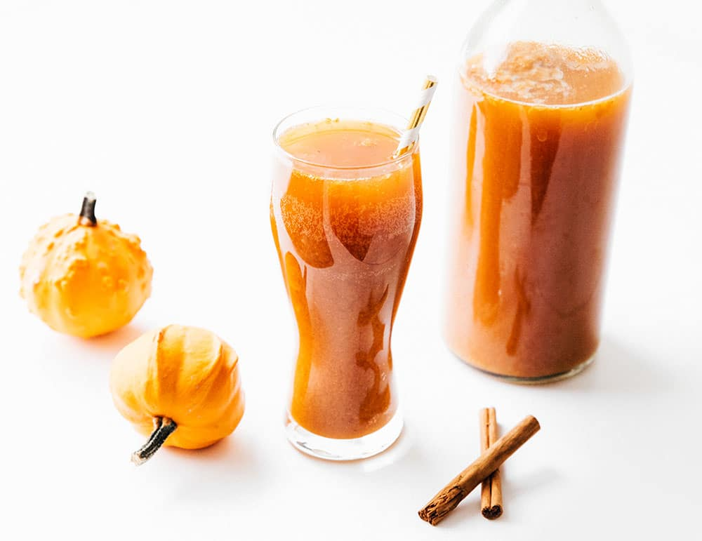 Pumpkin spice kombucha in a glass on white background