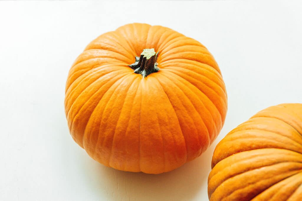 A traditional pumpkin on a white background with a second pumpkin peeking into the bottom right corner of the frame