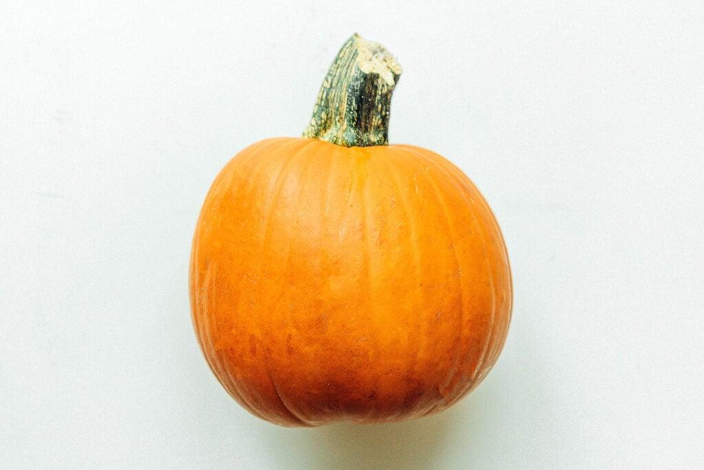 A pie pumpkin lying sideways on a white background