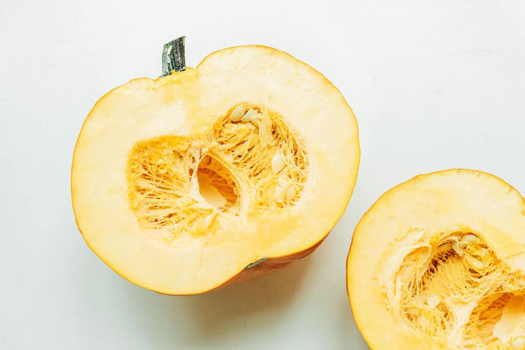 Two halves of a pie pumpkin facing inside up, displaying the center