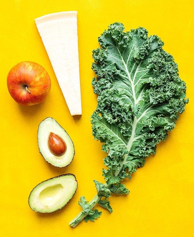 Ingredients to make kale salad on yellow background