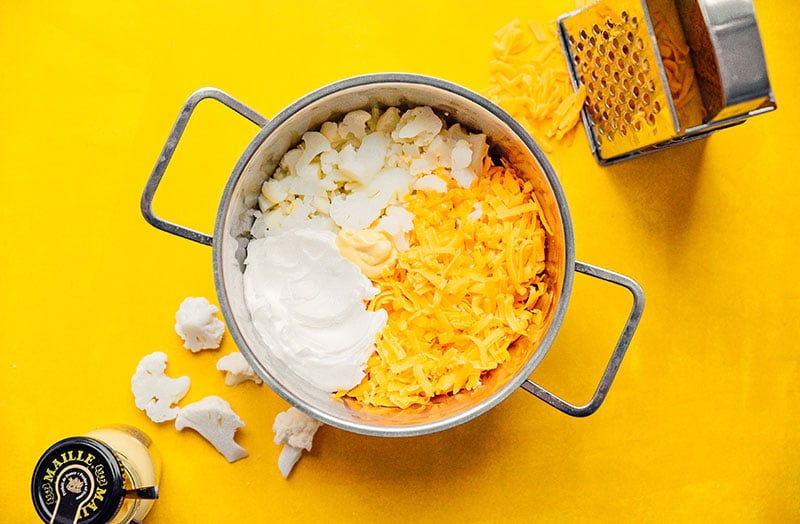 Ingredients to make cauliflower macaroni and cheese on a yellow background