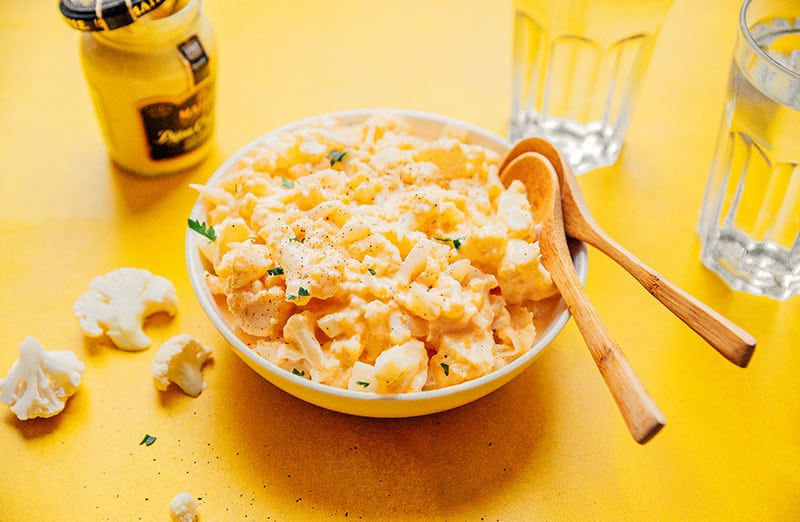 Keto mac and cheese in a bowl on a yellow background