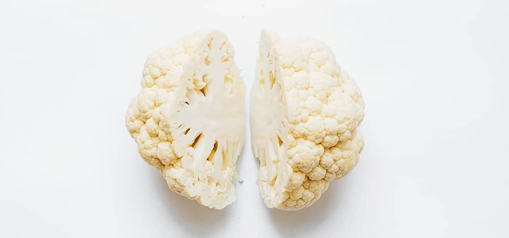 Cauliflower cut in half on a white background
