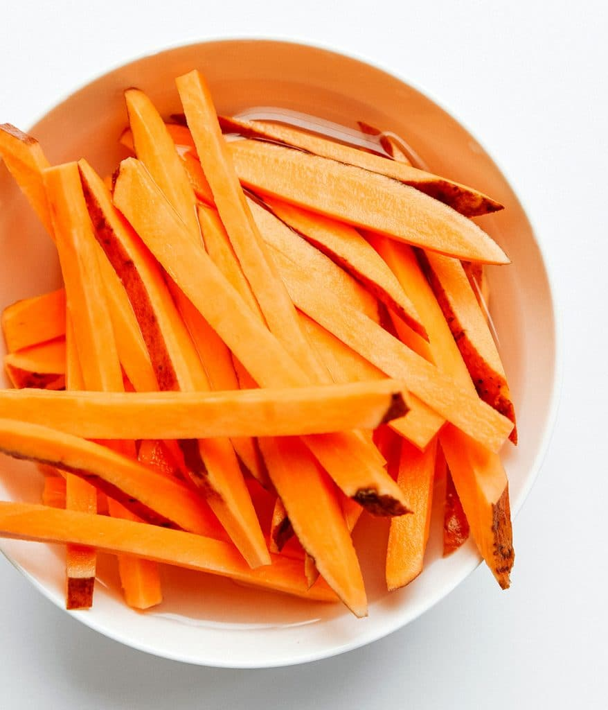 Soaking sweet potato fries in water to remove starch