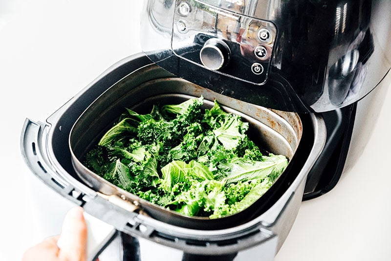 Kale in an air fryer on a white background