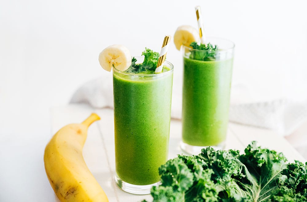 Kale green smoothie in a glass with paper straw