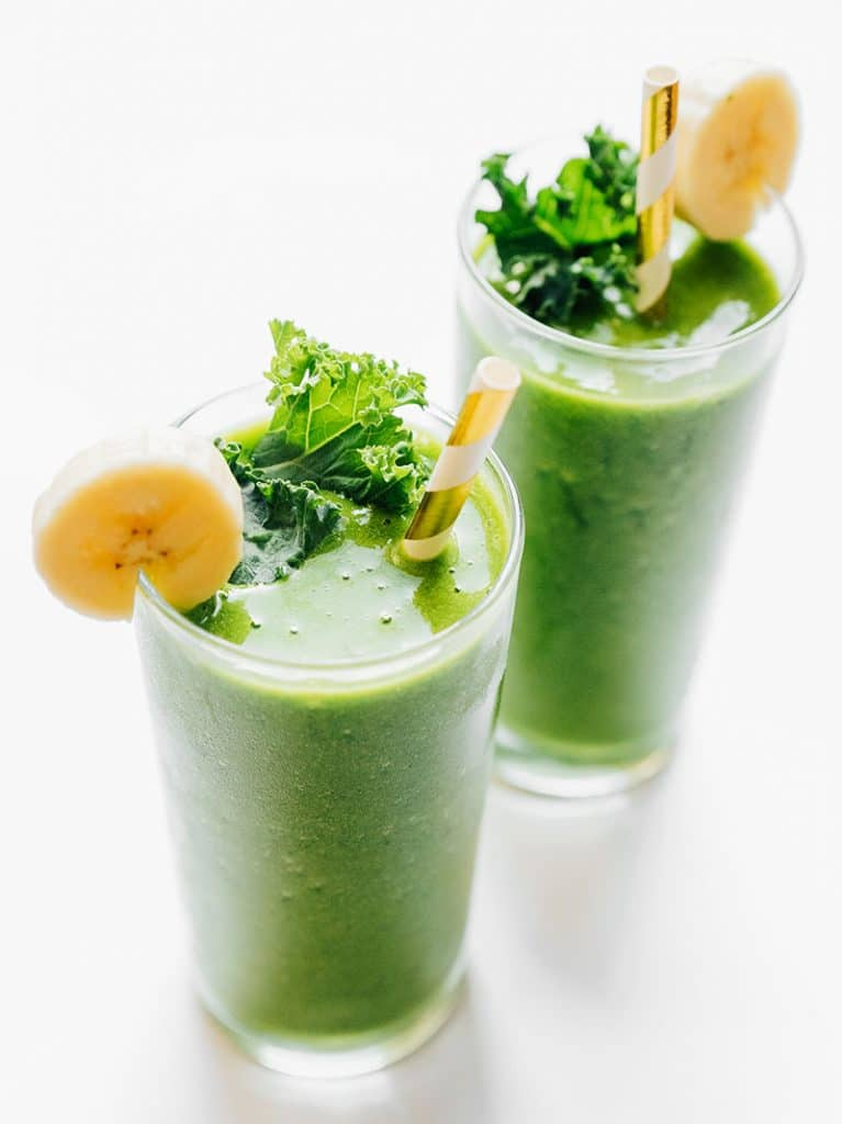 Green kale smoothie in a glass with paper straw