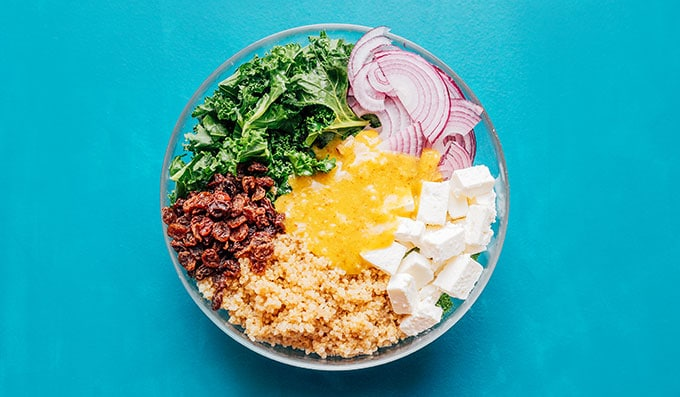 Ingredients for quinoa kale salad in a bowl on a blue background