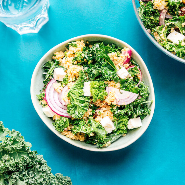 Quinoa kale salad in a bowl on a blue background